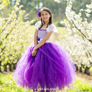 Girl in magnificent Jacaranda flower girl dress amongst blossoming cherry trees