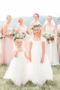 Two girls in Annabelle dress in front of a bride with bridesmaids