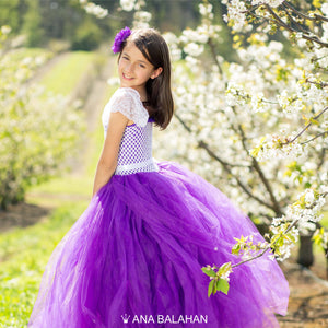 A girl in purple fluffy dress in spring garden