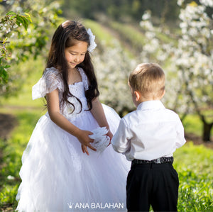 Cute girl in white jasmine blossom tutu dress and handsome boy in smart suit playing with a flower