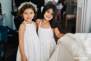 Two pretty girls in Florence dress and floral wreath prepare to be flower girls at a wedding