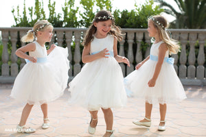 Three pretty flower girls in ivory color dresses and blue sashes