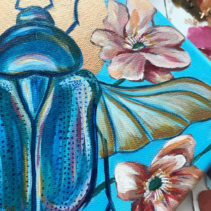 scarab beetle painting with flowers and copper halo close up