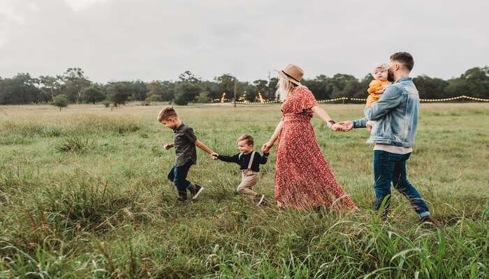 a woman with a man and three children in a meadow