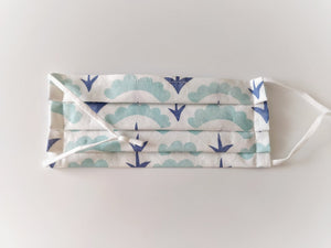 Face mask patterned with blue geometric shapes on a white background, with space for a nose piece and adjustable straps.