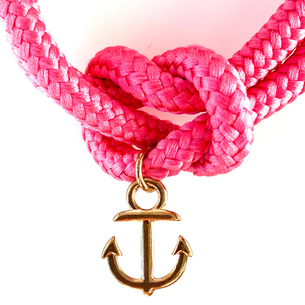 Closeup of the gold anchor charm  on the hot pink sailor knot bracelet