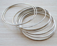 Set of 12 delicate silver bangles