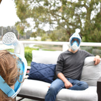 Two friends outside on a patio, wearing their Narwall Masks while sitting on a couch.