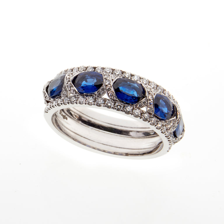 18ct white gold ring. Set with five oval blue sapphires and 0.52ct of pave set diamonds along each edge.