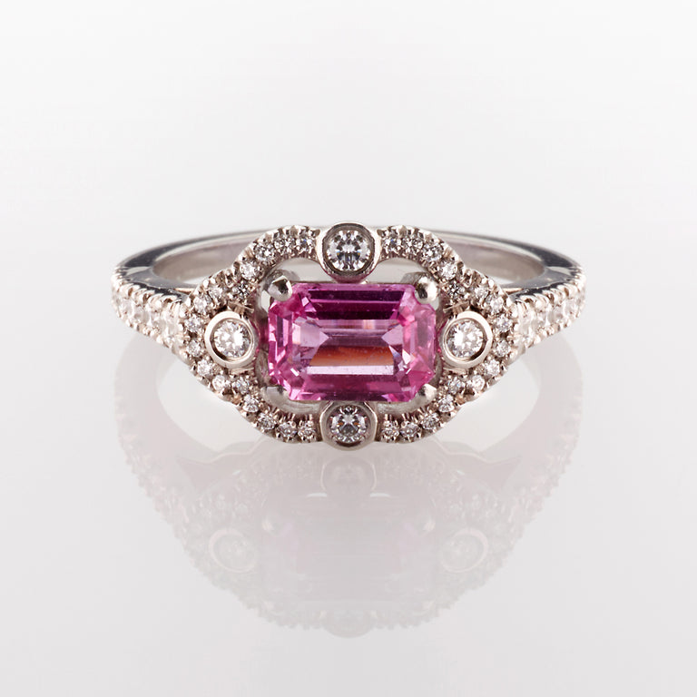 Emerald cut octagon pink sapphire surrounded by round cut brilliant diamonds. Part of the Ballerina collection.