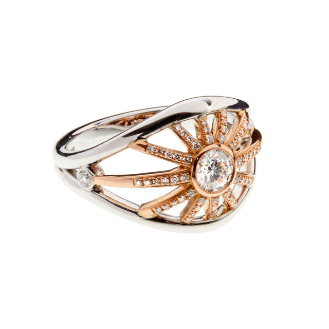 A diamond, white and rose gold ring with diamond studding spokes designed by Biagio Patalano for the Artistry collection.