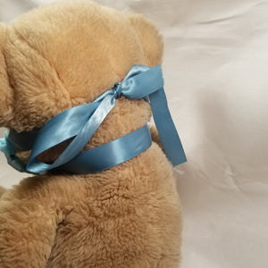 Soft satin ribbon goes around the back of the neck. The two tiable ends go over the ears (though not the bear's) and tie behind the head. It's one continuous piece of ribbon.