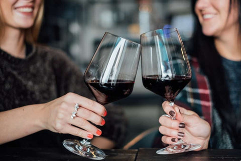 two happy woman holding glass of red wine