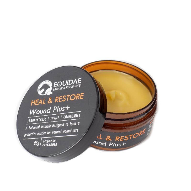 Tin of Heal and Restore wound ointment for horses being applied to horse with scratches on legs