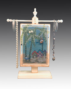earring holder with a hand painted beach design hanging on a jewelry tree