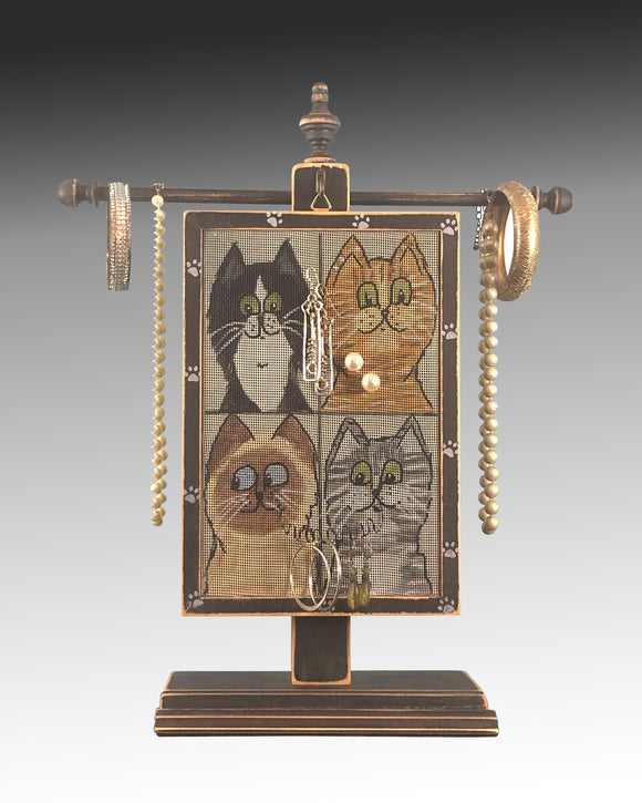 earring holder with cats design hanging on a jewelry tree