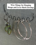wire thingy accessory holding hoop earrings in an earring holder