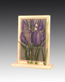 earring holder attached to a wood base with an iris design