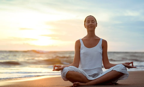 a woman meditating relaxly on a beach with sunset behind