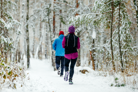 Two person running in the snow to keep joints healthy