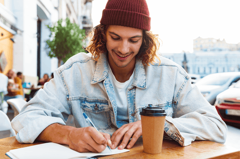 Young man sitting outside in a cafe writing in a journal