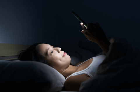 Young woman on phone in bed