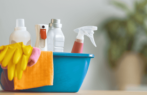 Bucket of cleaning products with a blurred background