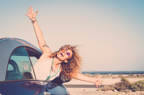 Happy woman leaning out of a car window by the beach