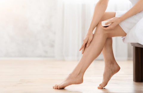 a woman applying cream on her leg to ease join discomfort