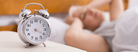 a person suffering from sleeplessness in bed while a clock ticking