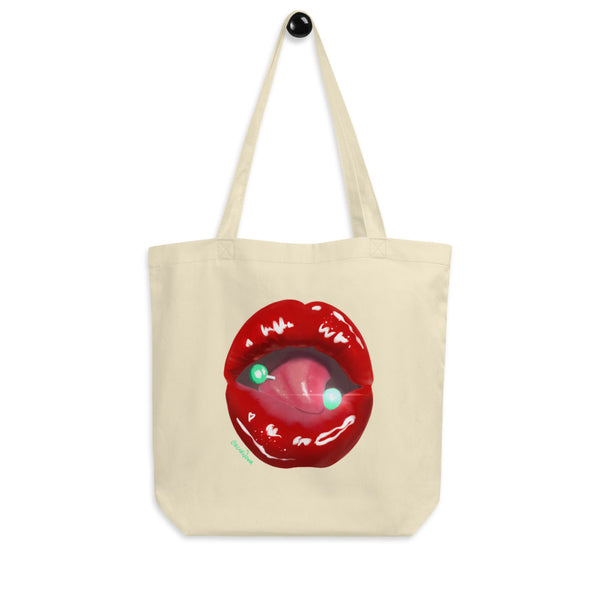 A cream eco tote bag printed with Acid Nova's Lips design. A pierced tongue licks a juicy pair of bright red lips.