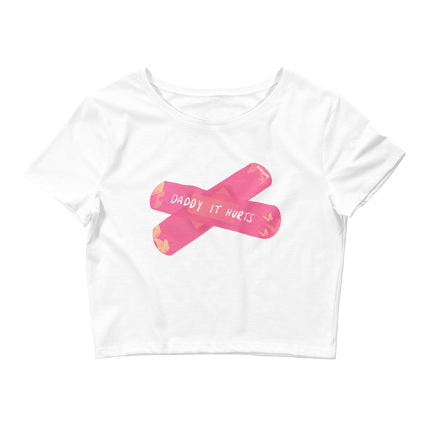 A white cropped T-shirt designed by Acid Nova. Printed with two overlapping pink plasters. The motif reads, Daddy it hurts.