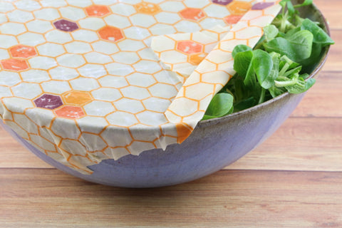 beeswax wrap being used on a container with salad