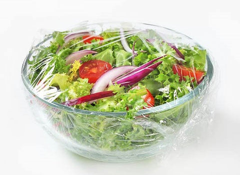 plastic wrap being used on a container with salad