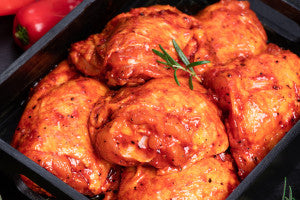 Chicken thighs. Raw chicken quilted in red, tomato marinade on a black plate and spices.Raw meat in the marinade.