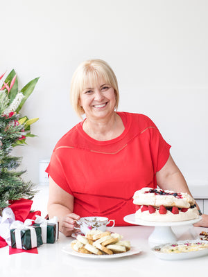 Woman smiling behind a table of Thermomix desserts