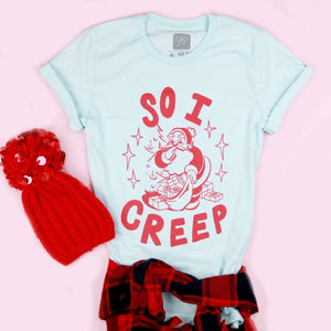 An image of the So I Creep Santa novelty Christmas shirt with a hat from Saturday Morning Pancakes.
