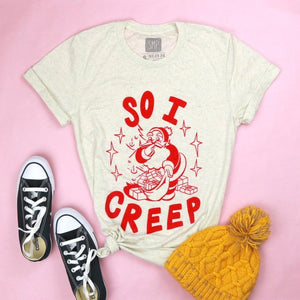 An image of the So I Creep Santa novelty Christmas shirt with props from Saturday Morning pancakes.