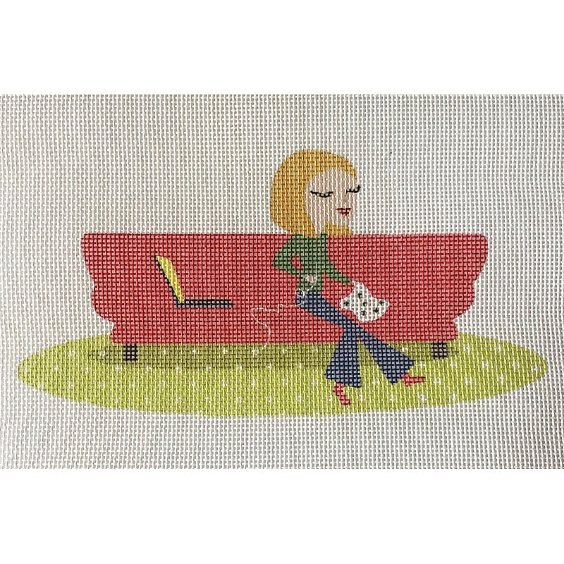 Needlepoint-for-fun stitcher on red sofa