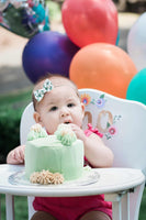 little girl eating a green cake in a white high chair