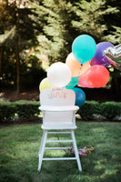 white high chair on grass with rainbow colored balloons attached