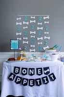 Bone appetit food table at a puppy themed birthday party with bone hanging garland
