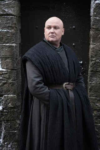 Varys from Game of Thrones standing in black clothes