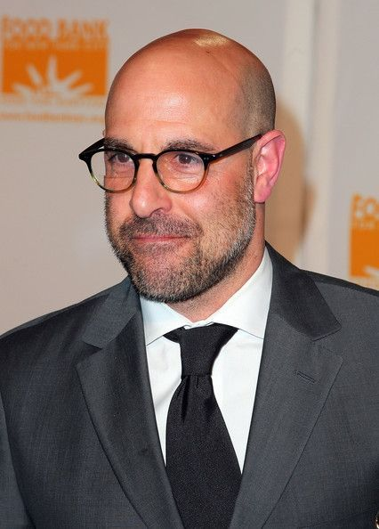 Stanley Tucci bald with reading glases