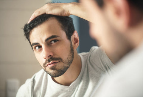 Man with full of hair staring at himself through the mirror