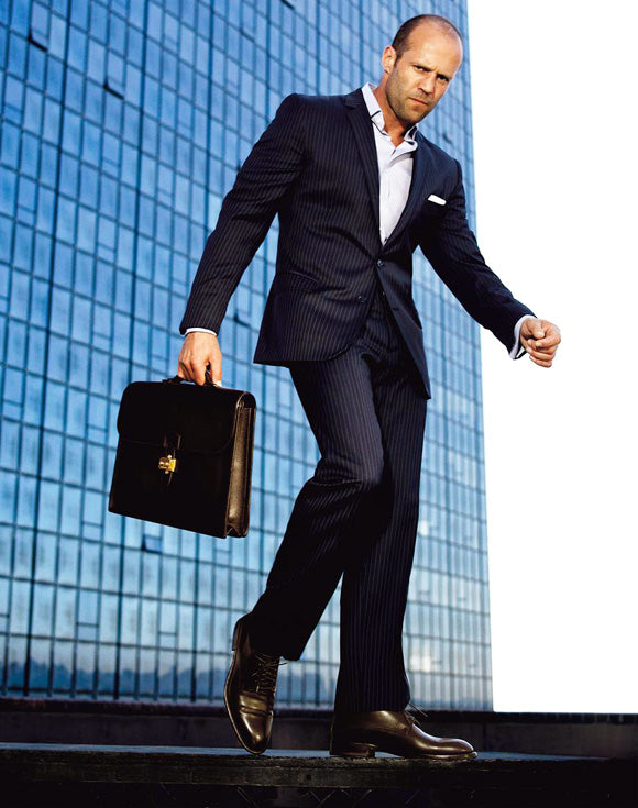 jason statham in formal wear with a case in his hand