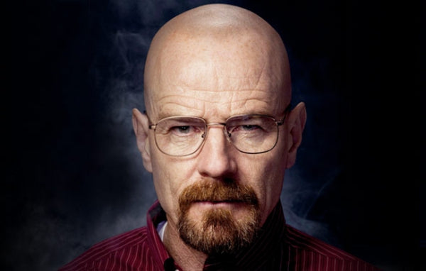 Bryan Cranston bald with beard and reading glasses