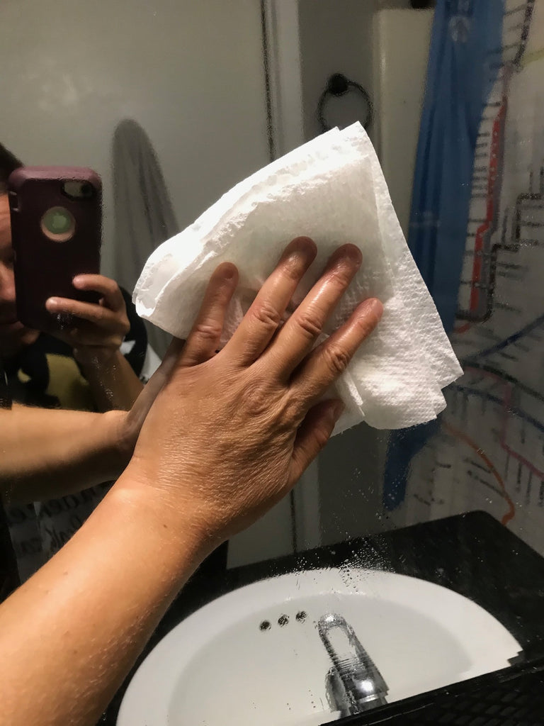 Using a paper towel to wipe the bathroom mirror.