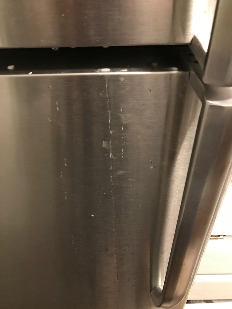 The smudged area around the refrigerator handle before it was cleaned.