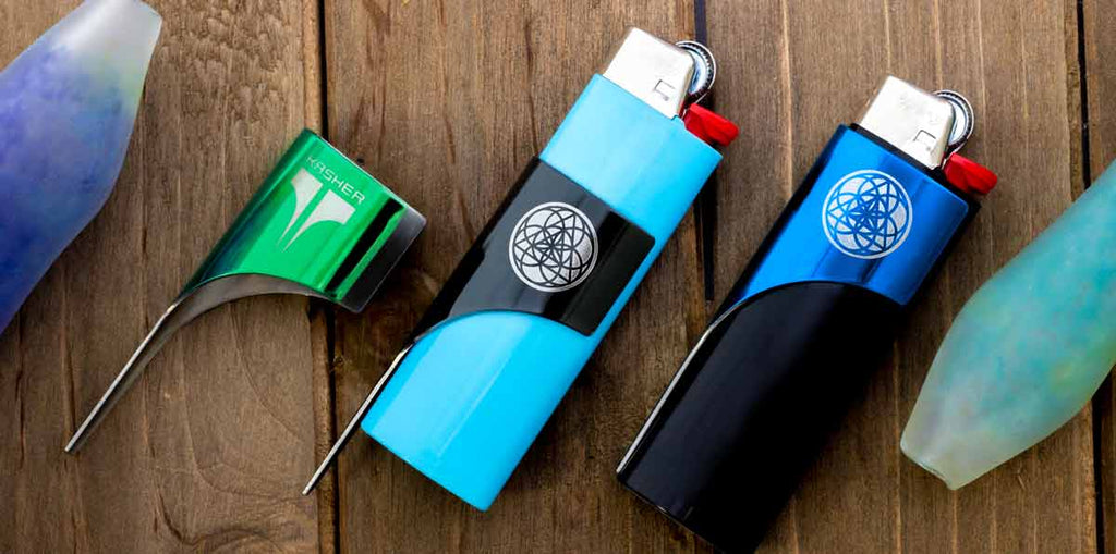 3 Kasher Lighter Tools with wooden background. Left to right description: Green Kasher engraved with Kasher shield with no lighter, Black Sacred Geometry engraving style Kasher on a light blue Bic lighter partially slid down, and a blue sacred geometry style engraved Kasher on a black lighter.